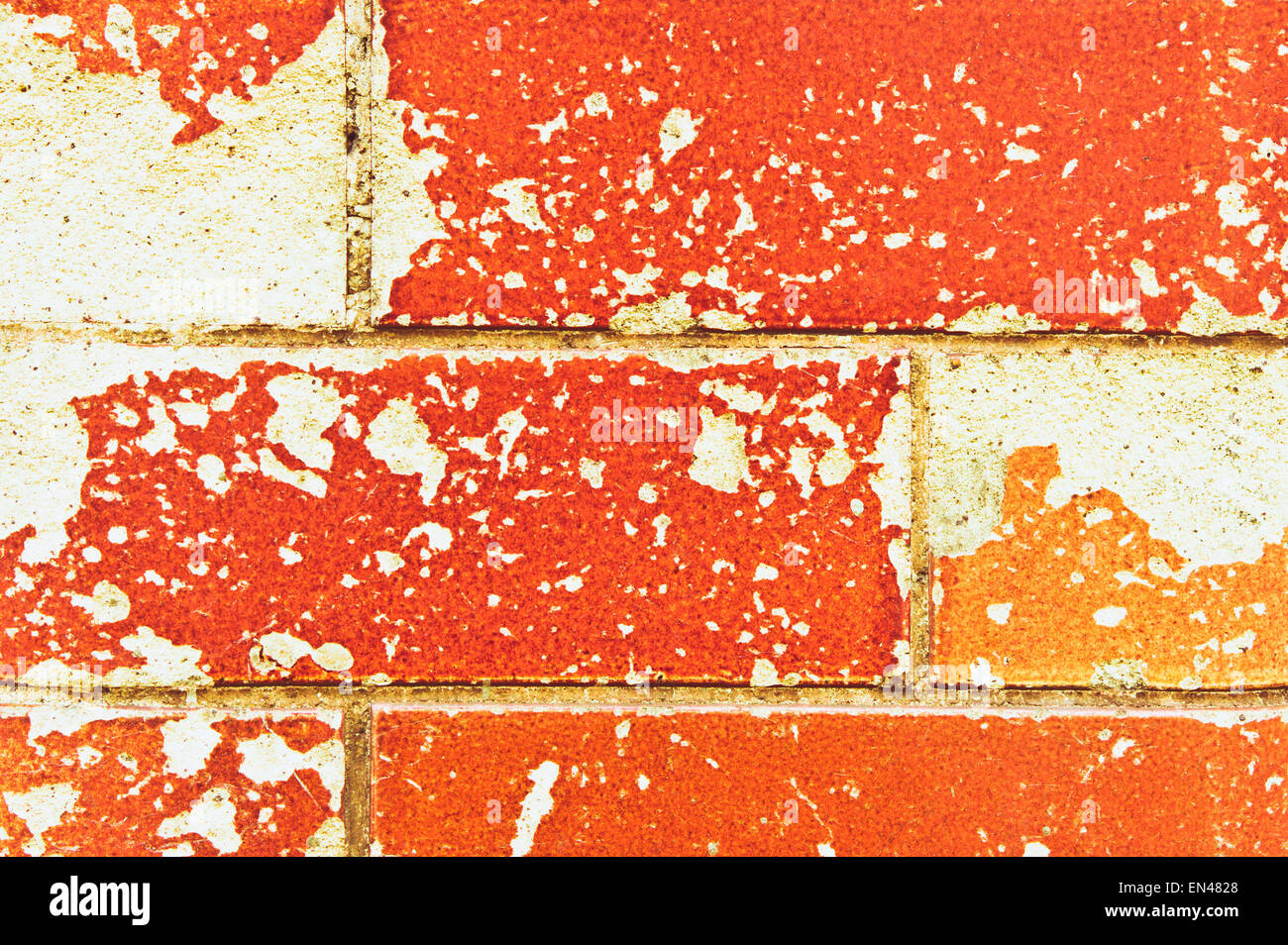 Glazed brown bricks damages exposing underlying stone Stock Photo