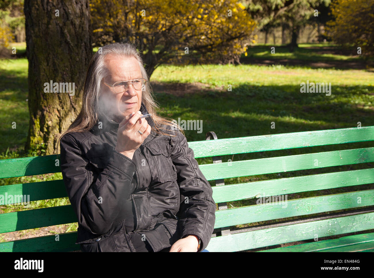 elderly gray-haired man in glasses, black jacket smoking a cigarette sitting on a bench in city park on sunny spring Stock Photo