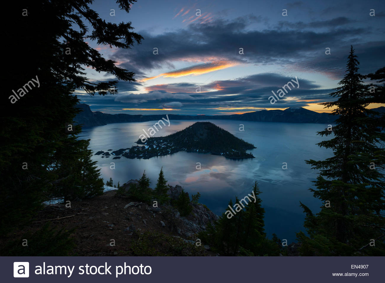 A hint of golden sunrise shines through the dark storm clouds hovering over Crater Lake in Crater Lake National - Stock Image