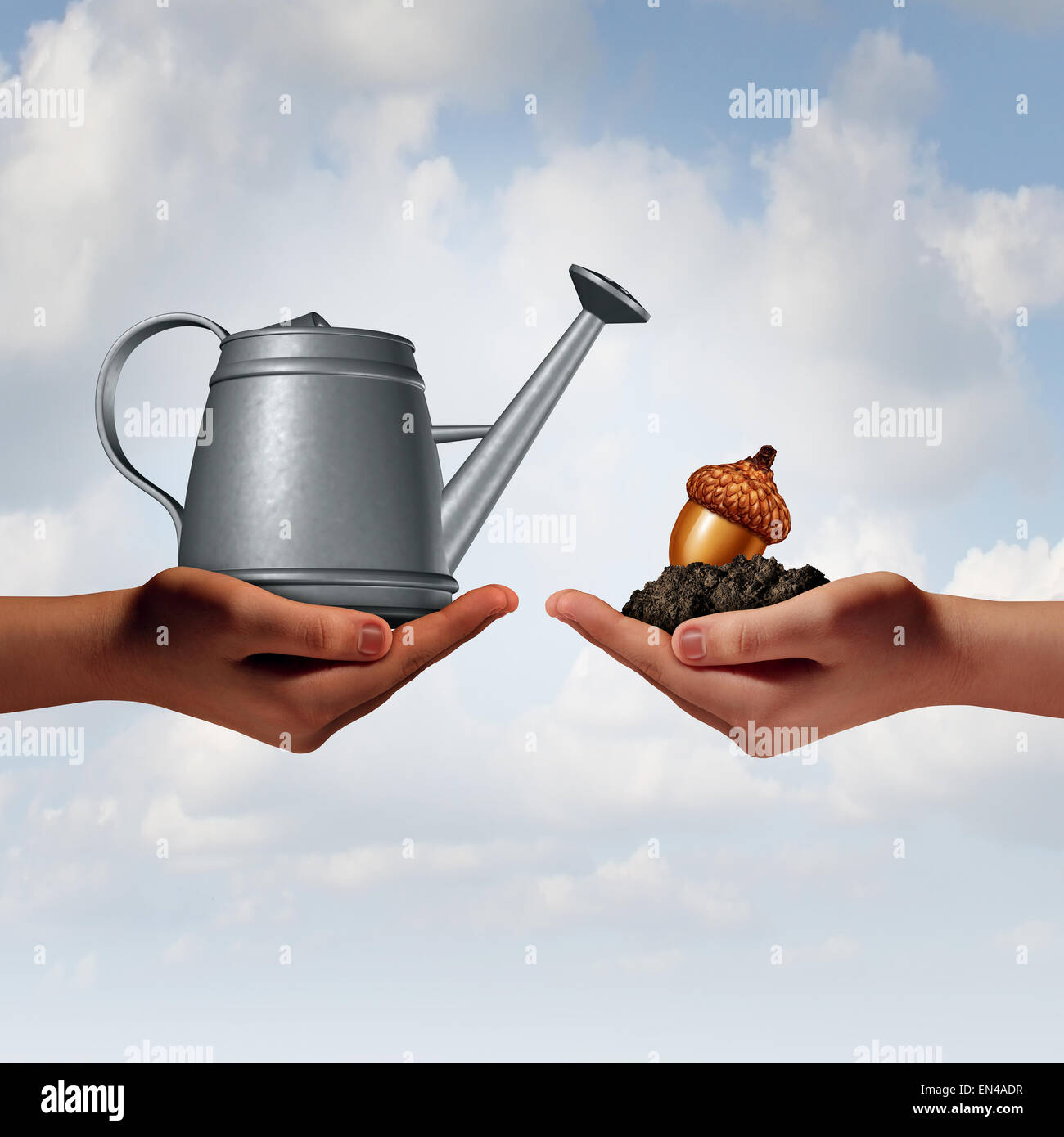Watering can investing business concept as a two diverse human hands holding a water pot and an acorn seed in fertile - Stock Image