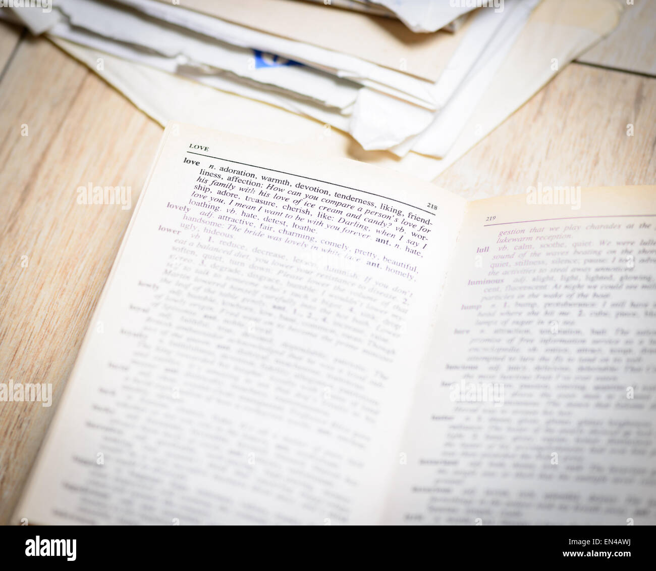 In the picture an open book where the word love is highlighted and its synonyms , the background of the letters Stock Photo