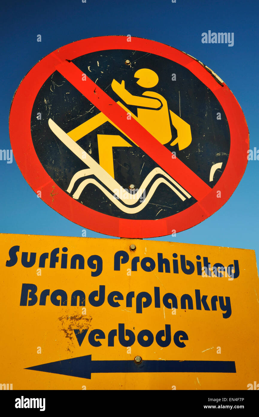 Weathered official notice board to surfers indicating surfing prohibited on section of beach reserved for swimmers, - Stock Image