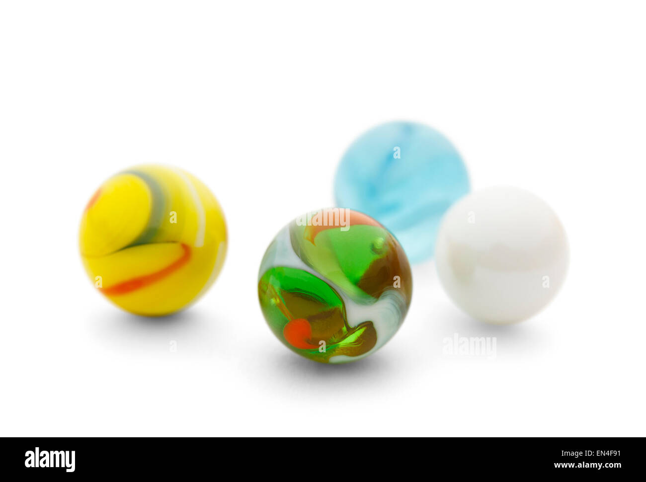 Four Toy Glass Marbles Isolated on a White Background. - Stock Image