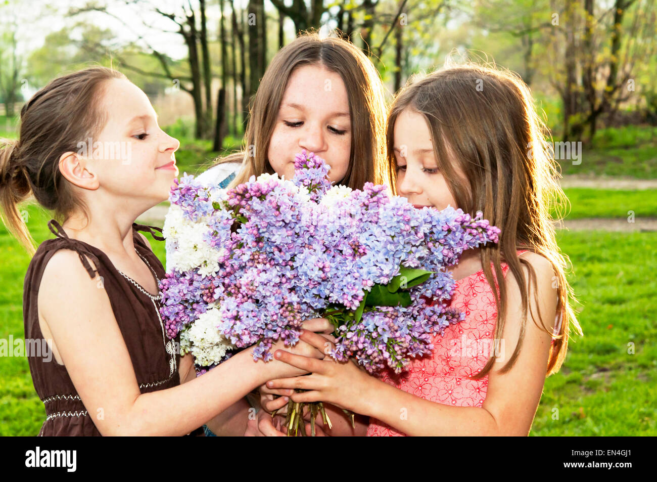 Three girls smelling Lilac bouquet together - Stock Image