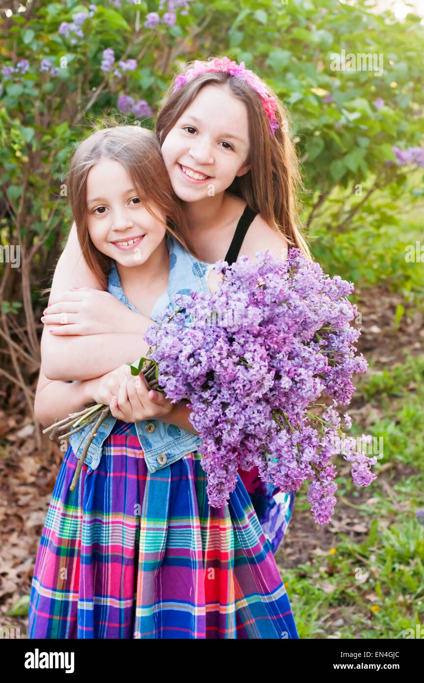 Two girls hug holding bouquet of Lilac flowers - Stock Image
