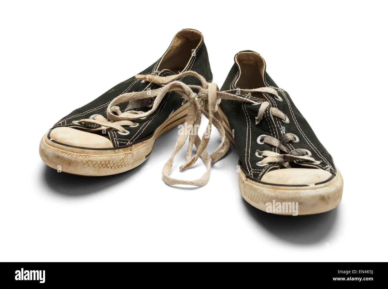 ff4ef80a44e3 Old Dirty Worn Pair of Canvas Shoes With Knotted Shoe Laces Isolated on White  Background.