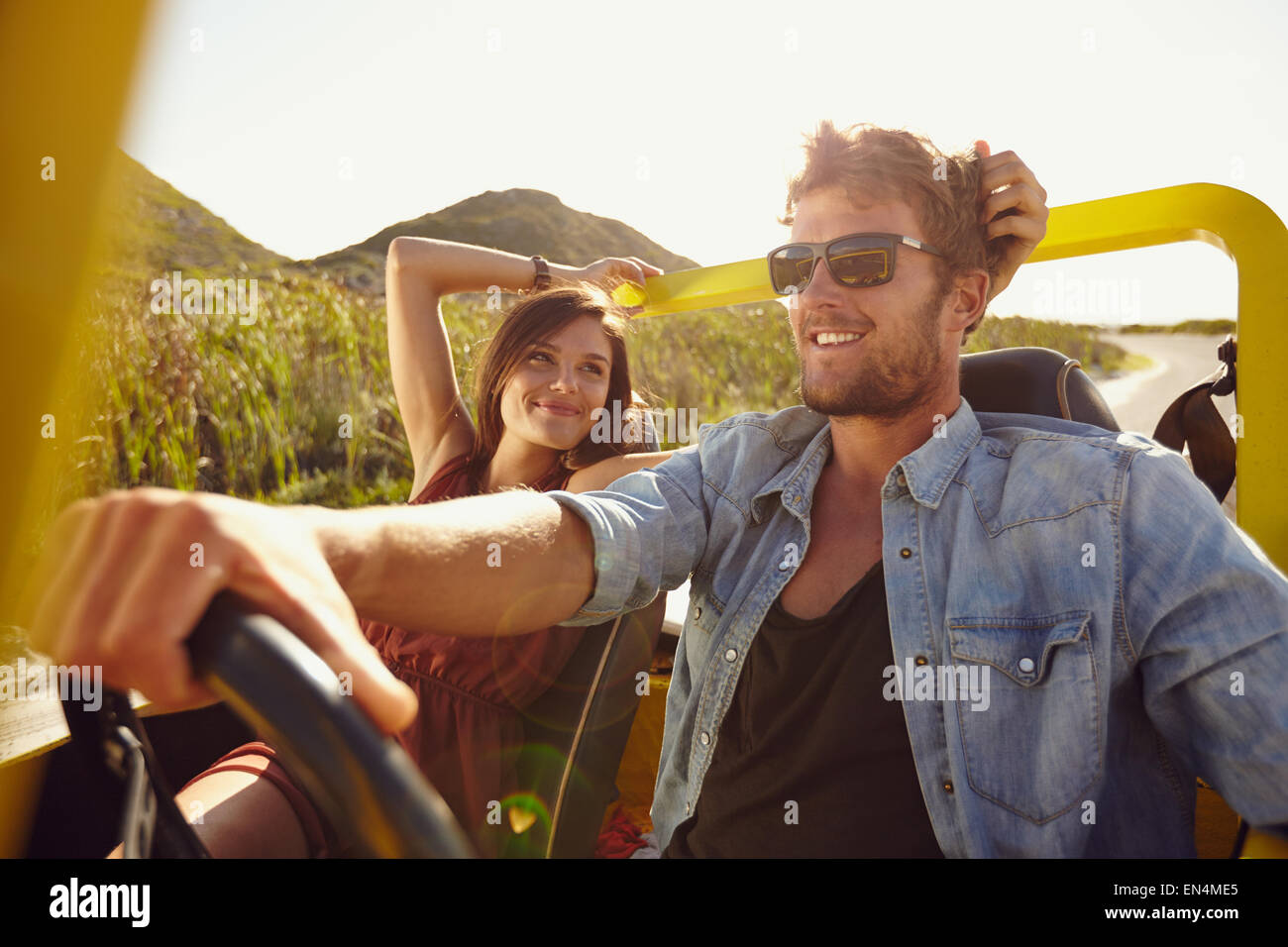 Woman looking at man driving car on a summer day. Loving young couple on road trip. - Stock Image