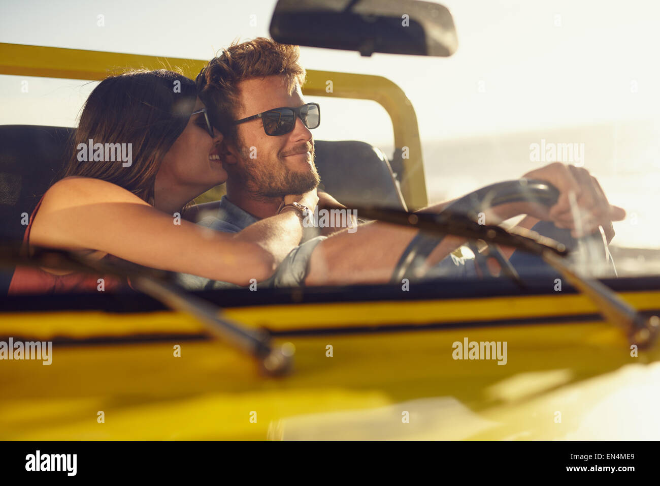 Romantic young couple sharing a special moment while on a road trip. Man driving car with girlfriend. - Stock Image