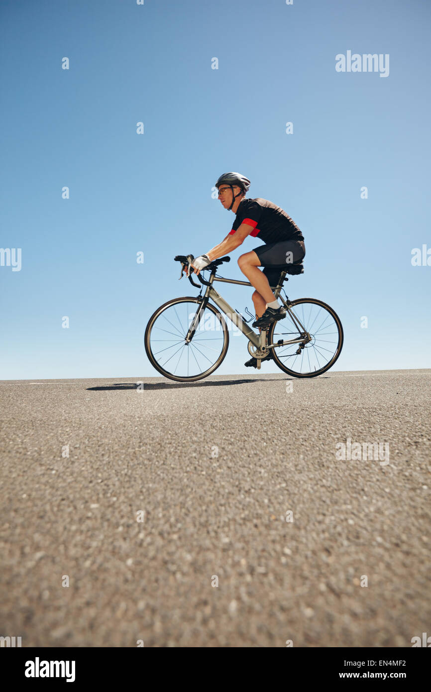 Side view of male cyclist riding bicycle on flat road against blue sky. Low angle view of caucasian triathlete training - Stock Image
