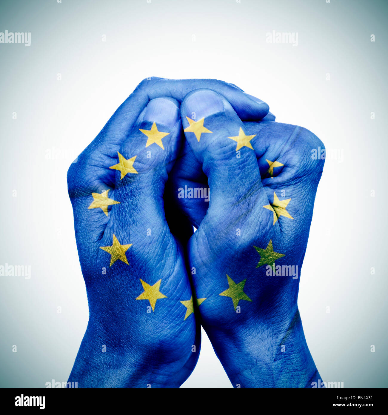 the clasped hands of a young man patterned with the flag of the european union - Stock Image