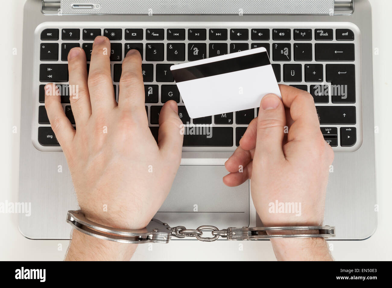 credit card cheater with handcuff on laptop - Stock Image