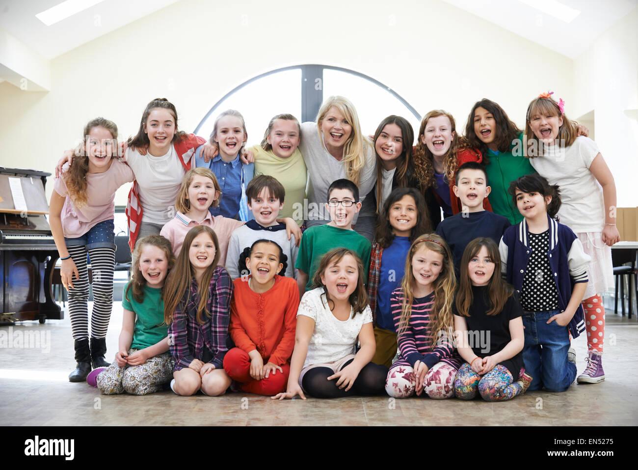 Large Group Of Children With Teacher Enjoying Drama Workshop Together - Stock Image
