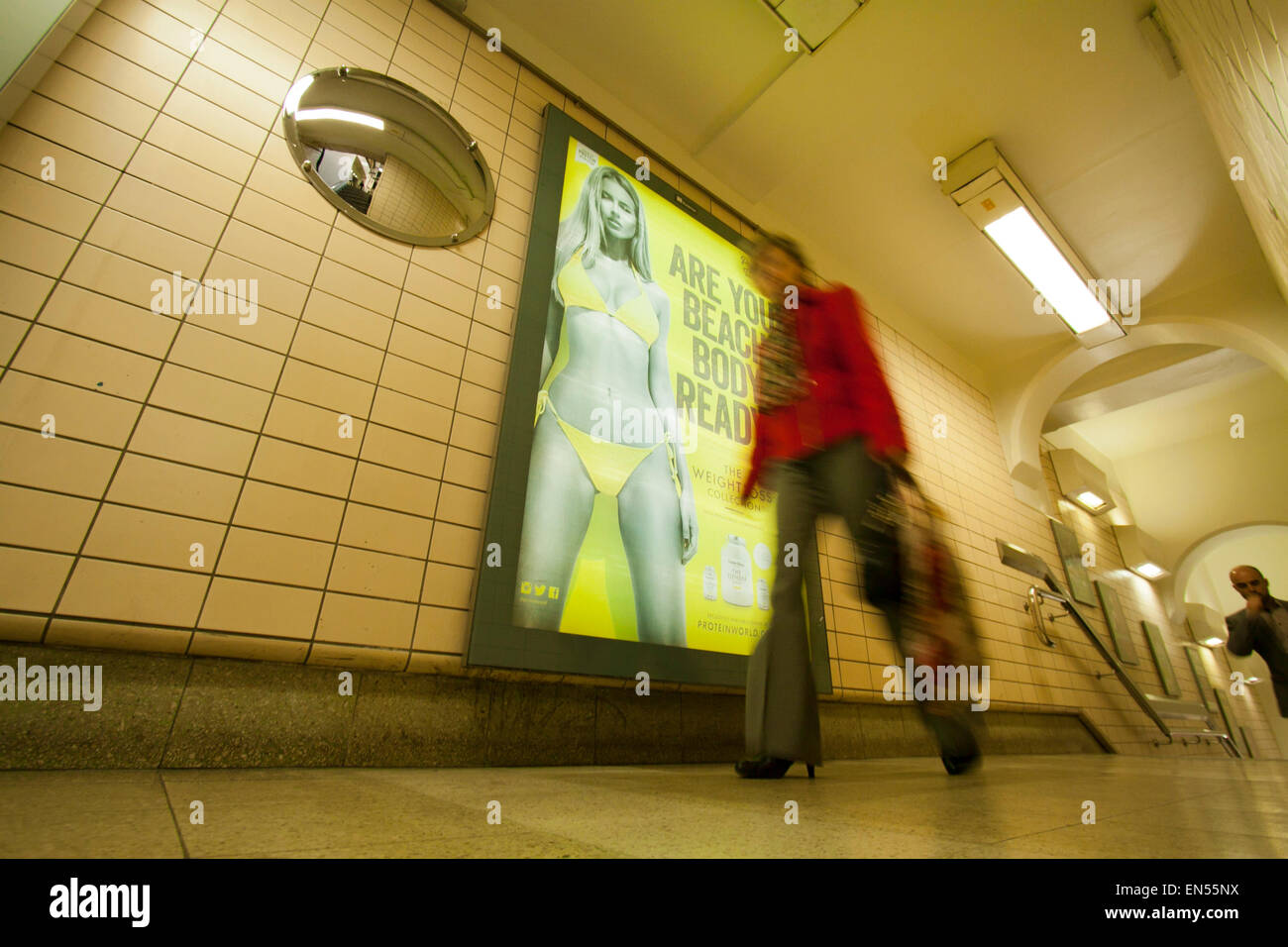London, UK. 28th April 2015. A dietary poster for World Protein featuring a slim woman wearing a yellow bikini has - Stock Image
