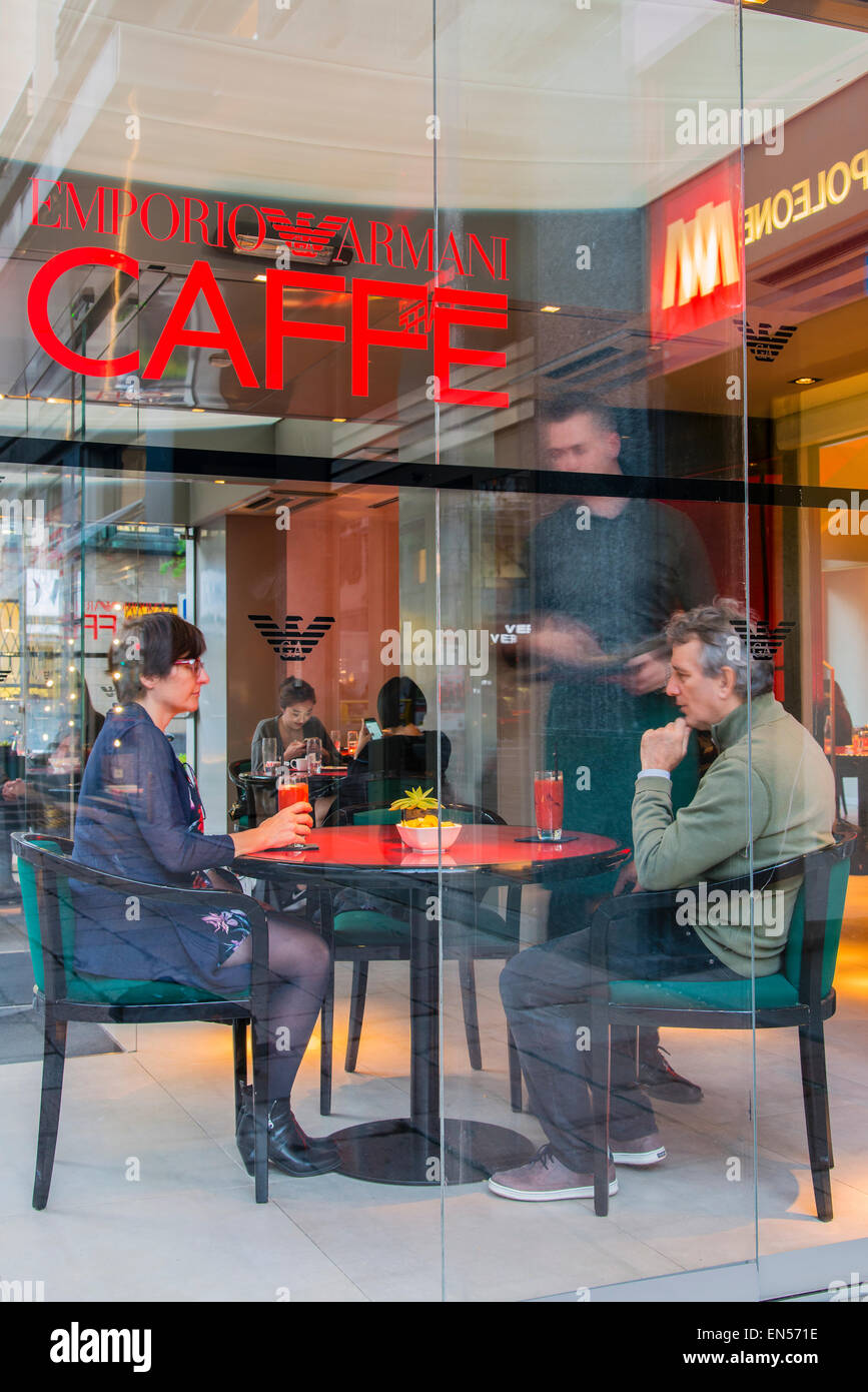 Tourists seated having an aperitivo drink at Emporio Armani Caffe, Milan, Lombardy, Italy - Stock Image