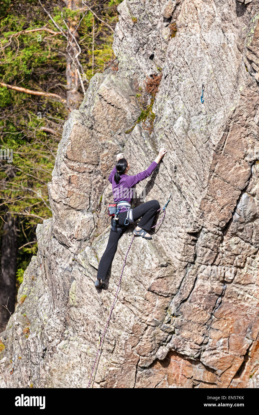 Female rock climber on a steep cliff. - Stock Image
