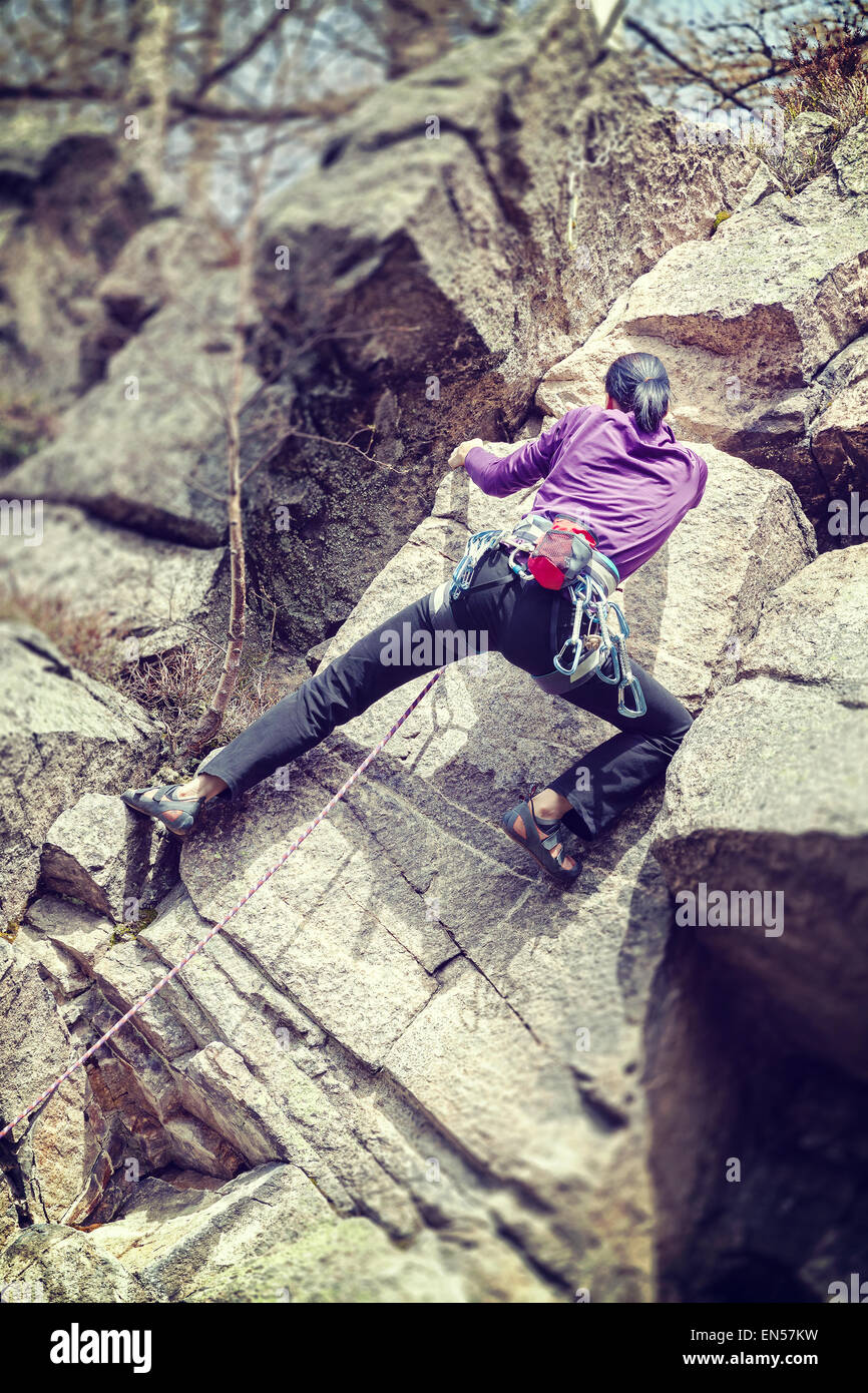 Retro filtered photo of a female rock climber, shallow depth of field. - Stock Image