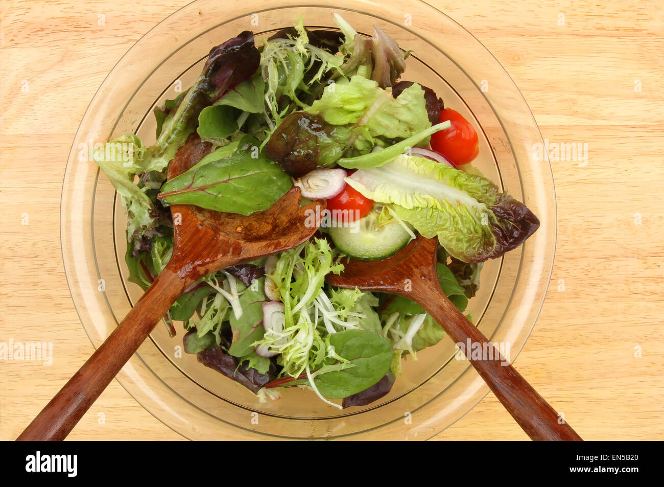 Mixed salad in a bowl with wooden salad servers - Stock Image