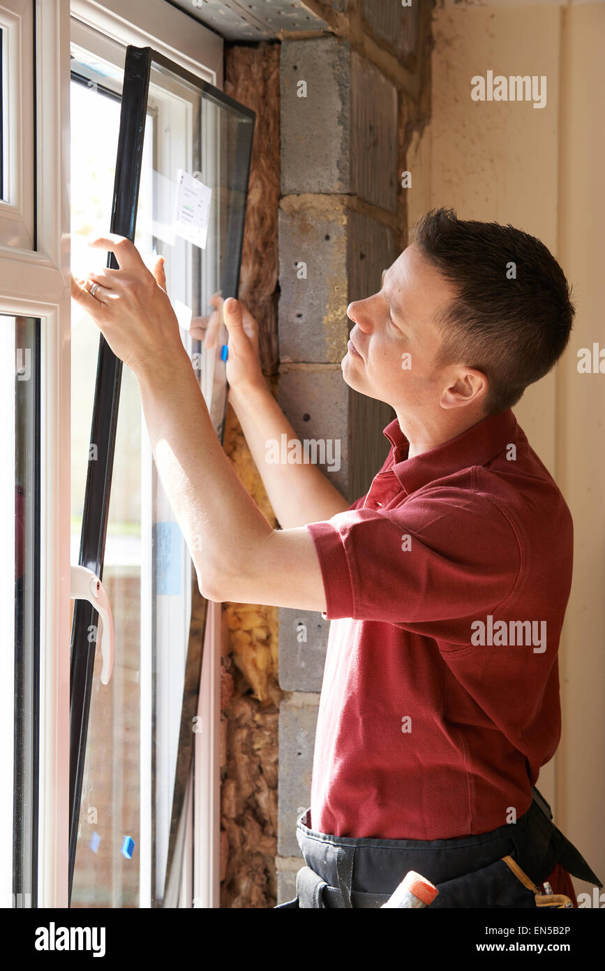 Construction Worker Installing New Windows In House - Stock Image