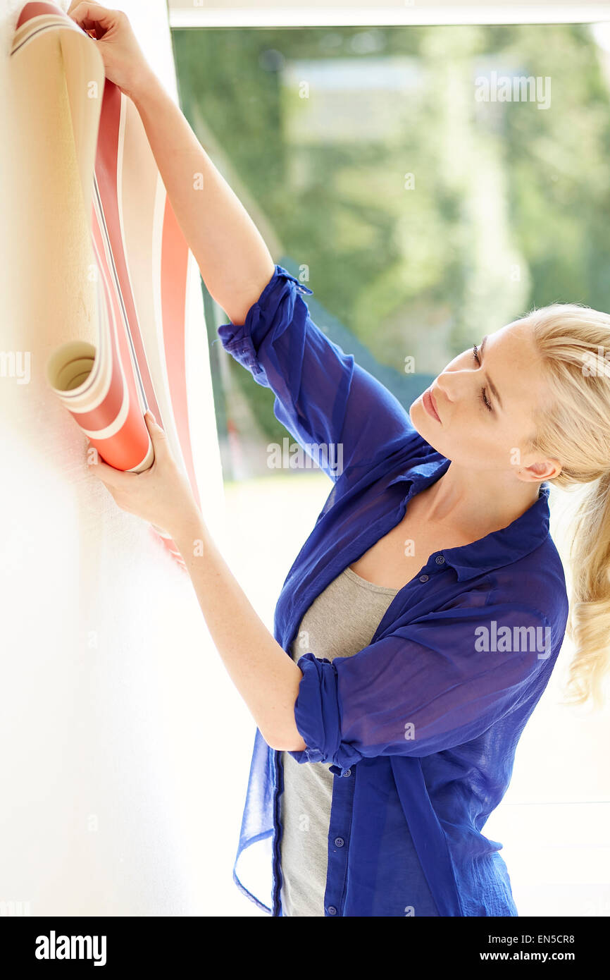 Woman holding up wallpaper sample - Stock Image