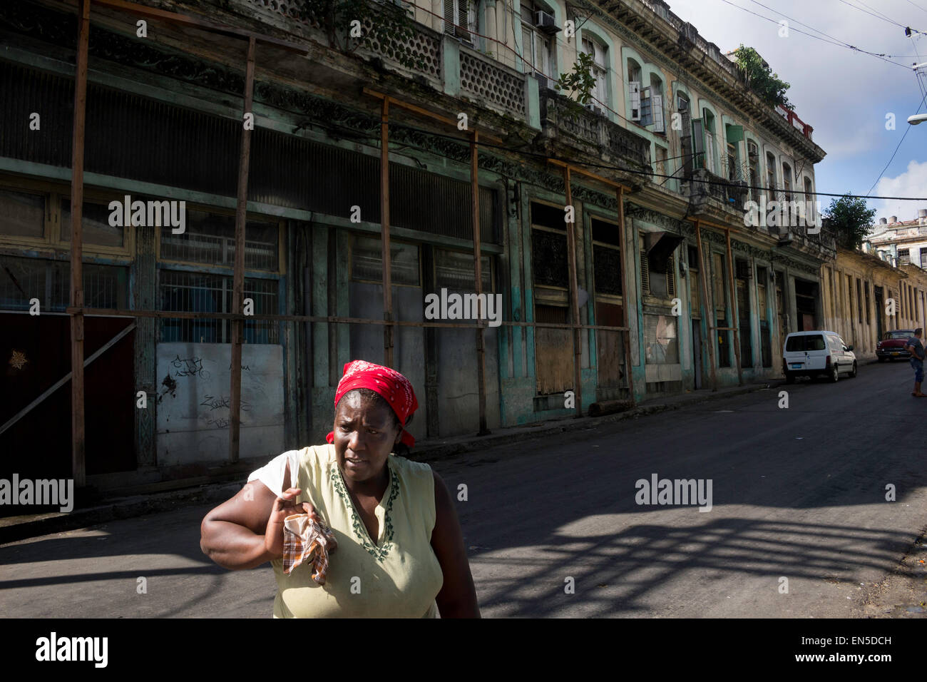 Cuban woman walking in street Havana with collapsing houses underpin by wooden masts - Stock Image