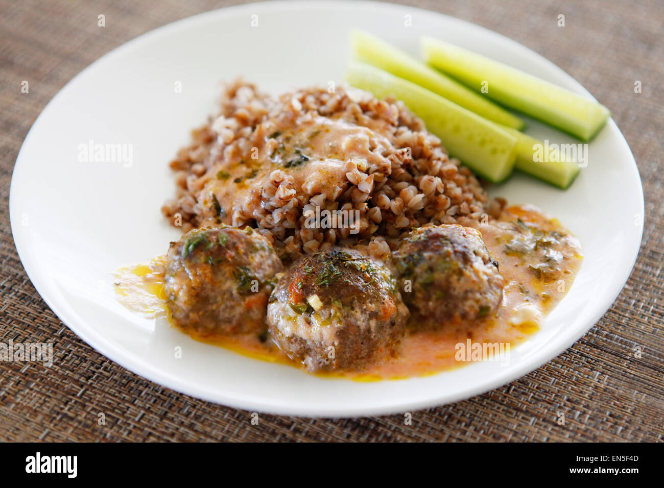 Buckwheat with small meat balls, red souse and fresh cucumbers - Stock Image