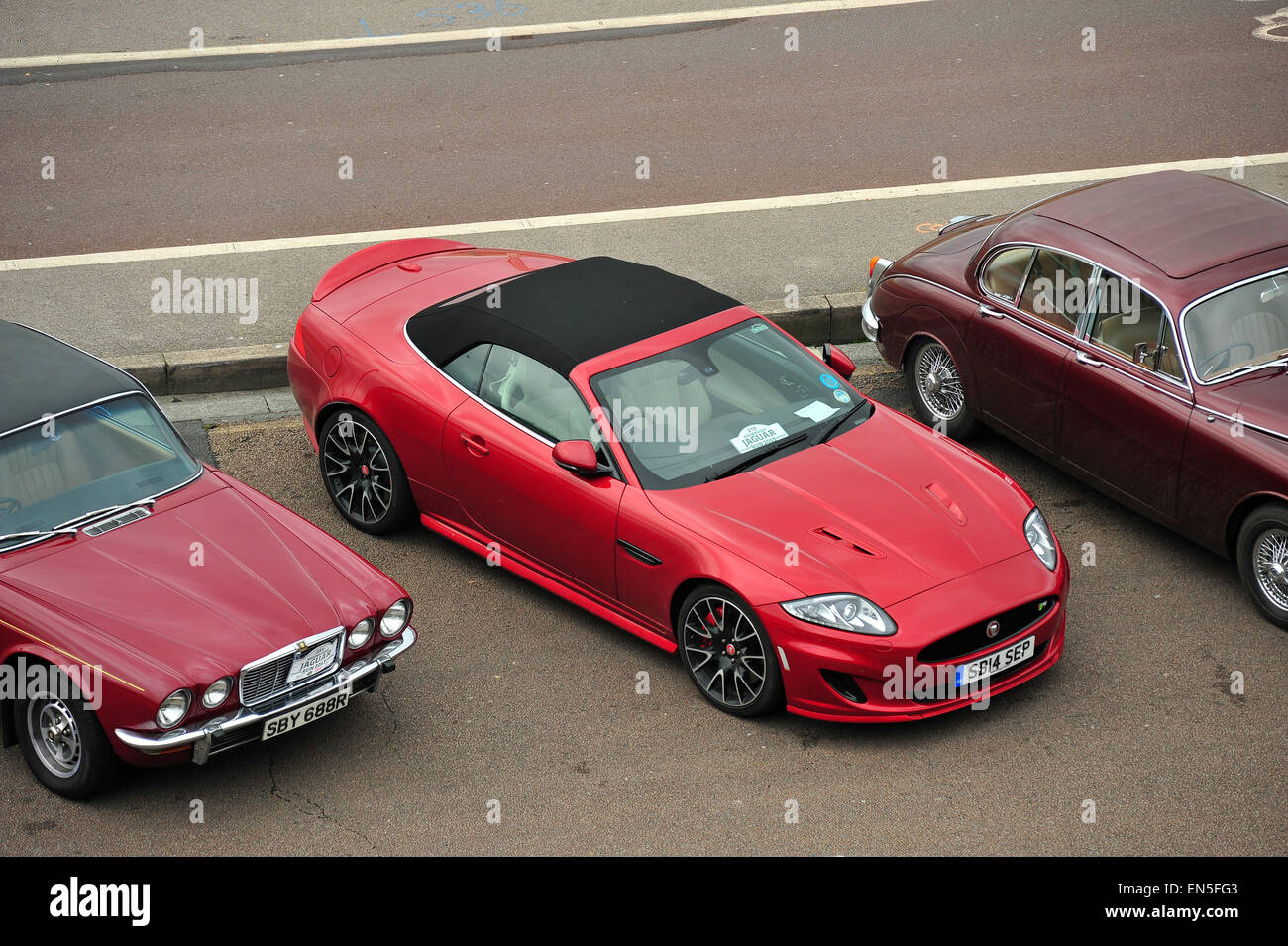 A row of red Jaguars parked along Madeira Drive in Brighton for the London to Brighton Jaguar Run. - Stock Image