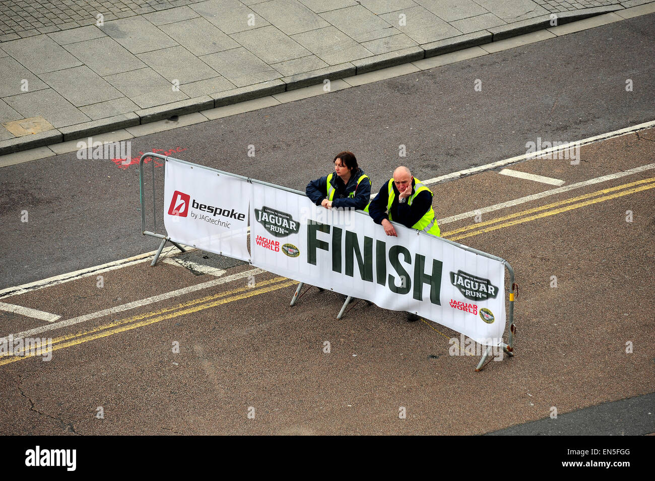 Two marshals at a classic car rally wait by the finish line to greet competitors in Brighton. - Stock Image
