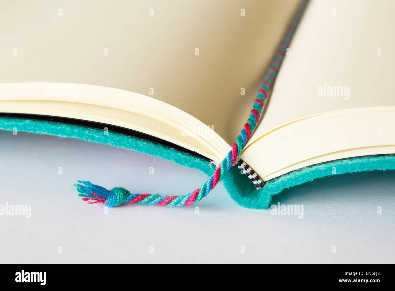 Open blank notebook with a bookmark marking the page on a plain surface with copy space on white background. - Stock Image