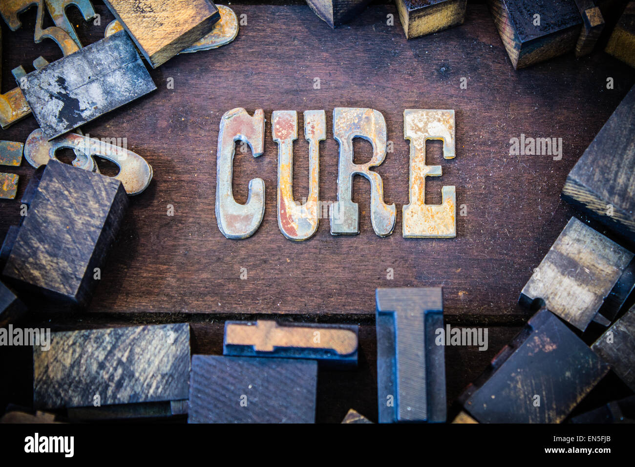 the word cure written in rusted metal letters surrounded by vintage wooden and metal letterpress type