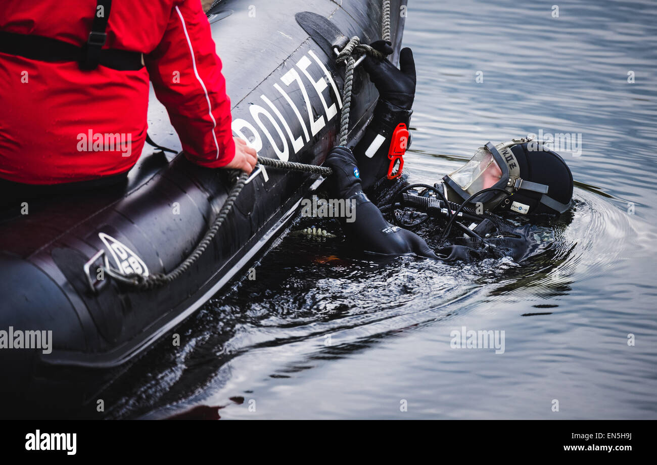 A police diver holds on a inflatable dinghy in the dam Pirk, Germany, 28 April 2015. The criminal investigation - Stock Image