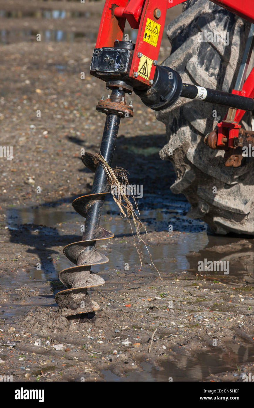 Tractor equipped with earth auger / earth drill / soil auger / mechanized post hole digger for drilling holes in - Stock Image