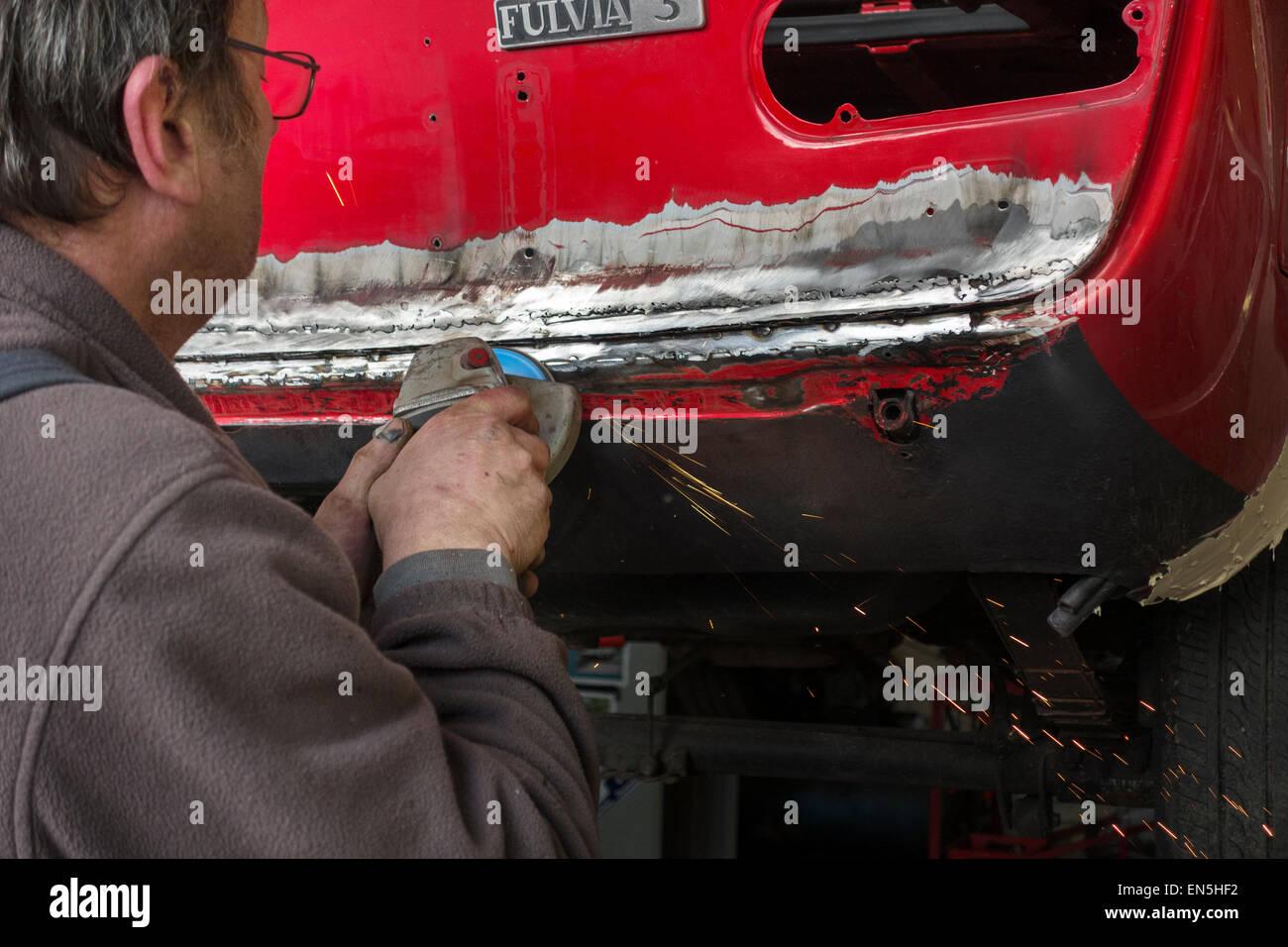 Car enthusiast grinding red oldtimer's coachwork / bodywork with angle grinder / side grinder / disc grinder - Stock Image
