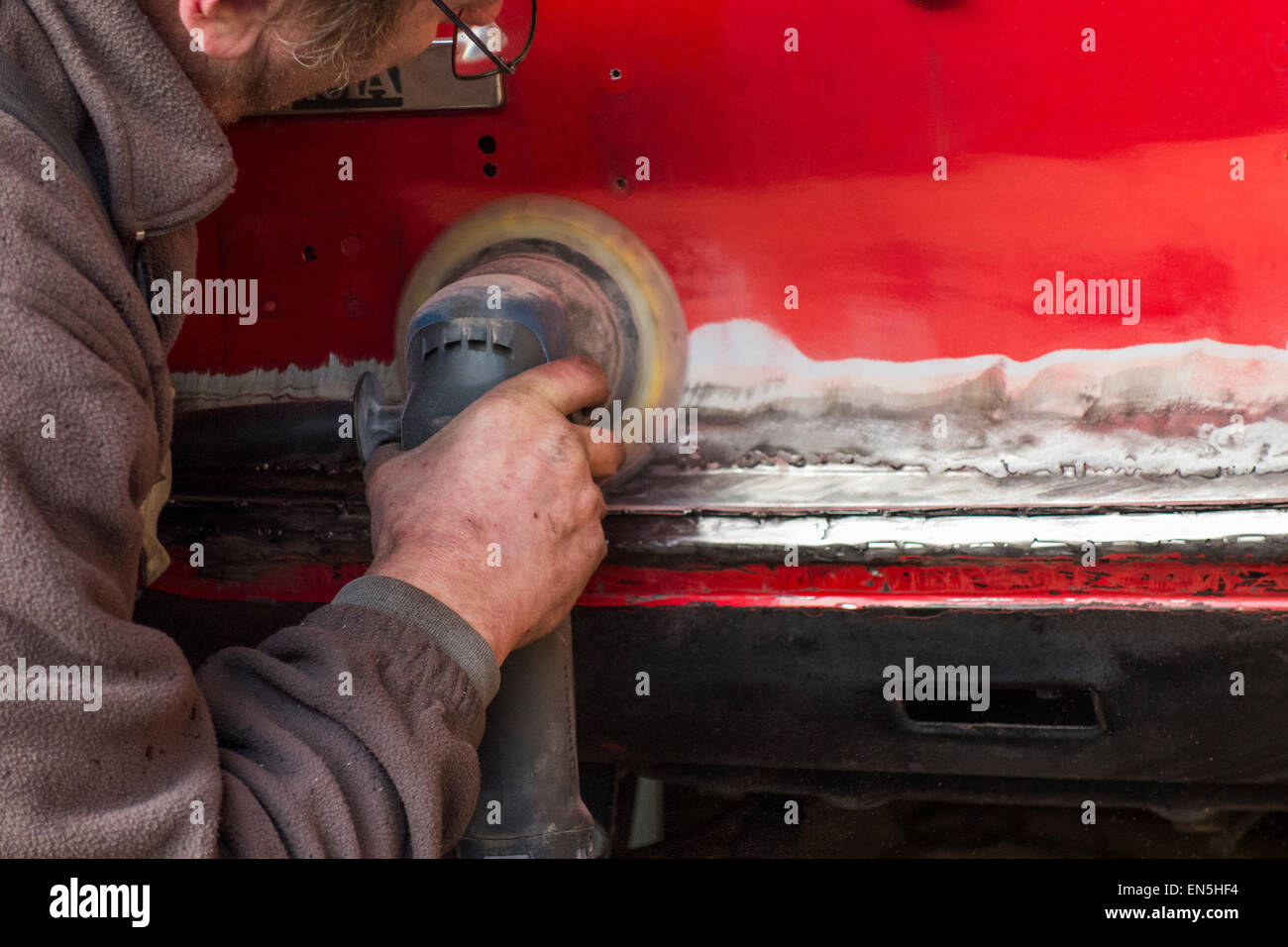 Car enthusiast polishing red oldtimer's coachwork / bodywork with angle grinder / side grinder / disc grinder Stock Photo