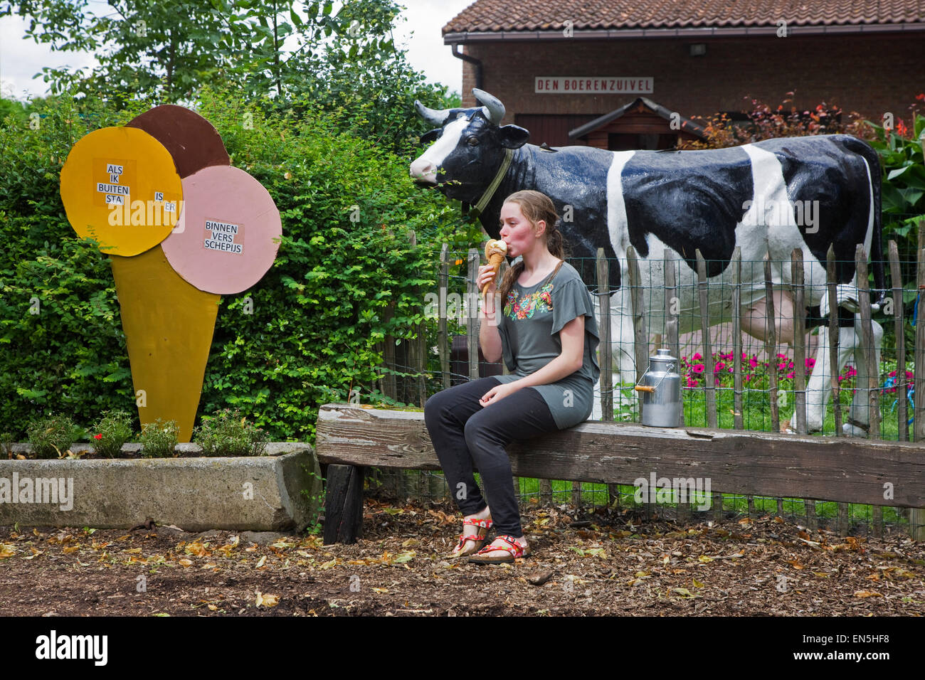 Girl eating dairy made ice cream in front of dairy farm - Stock Image