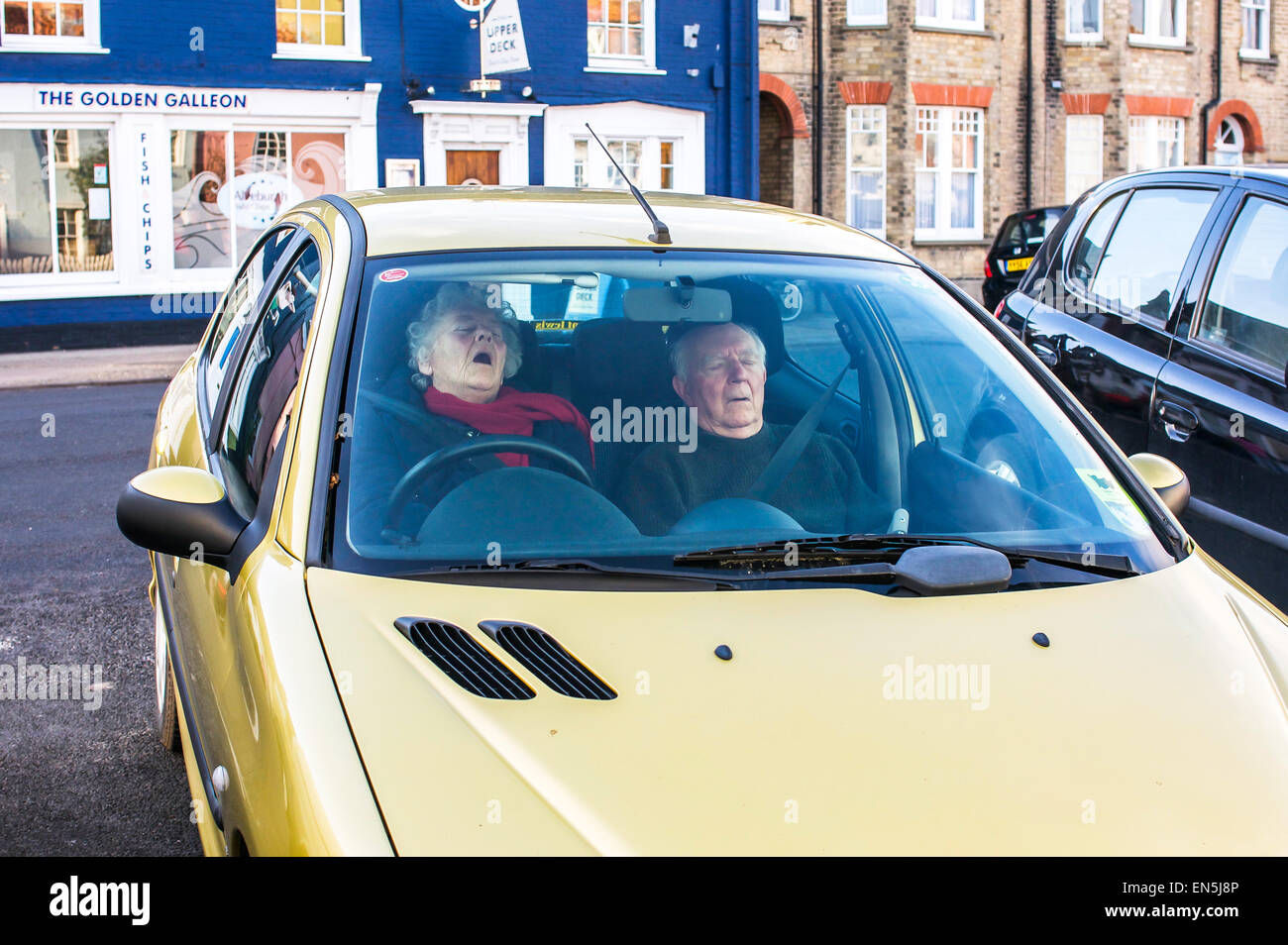 An older couple in England, apparently overwhelmed by the urge to sleep, parked the car, locked the doors, and did - Stock Image