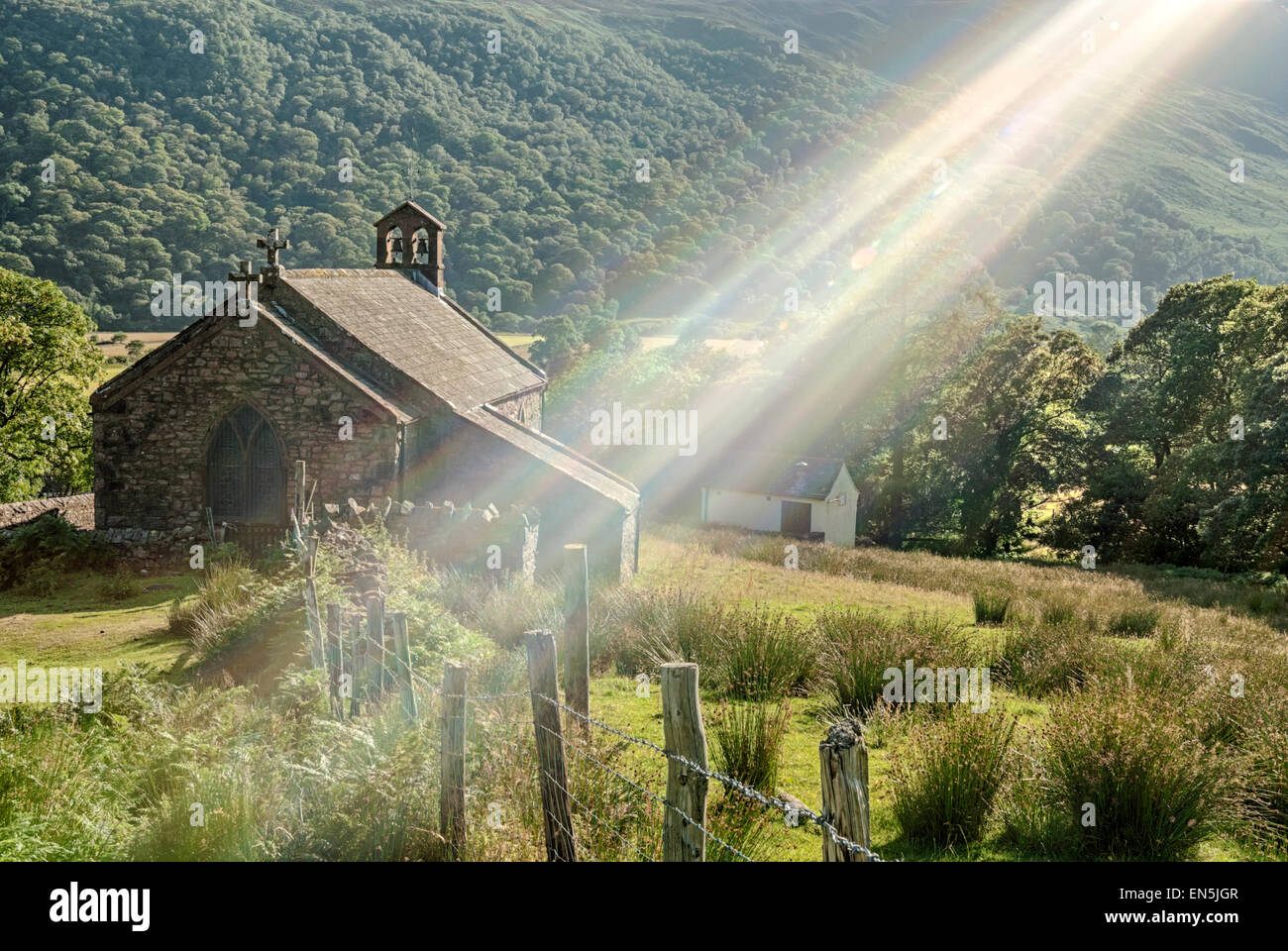 Village church of Buttermere backlit by a strong sunbeam, Lake District National Park, Cumbria, England - Stock Image