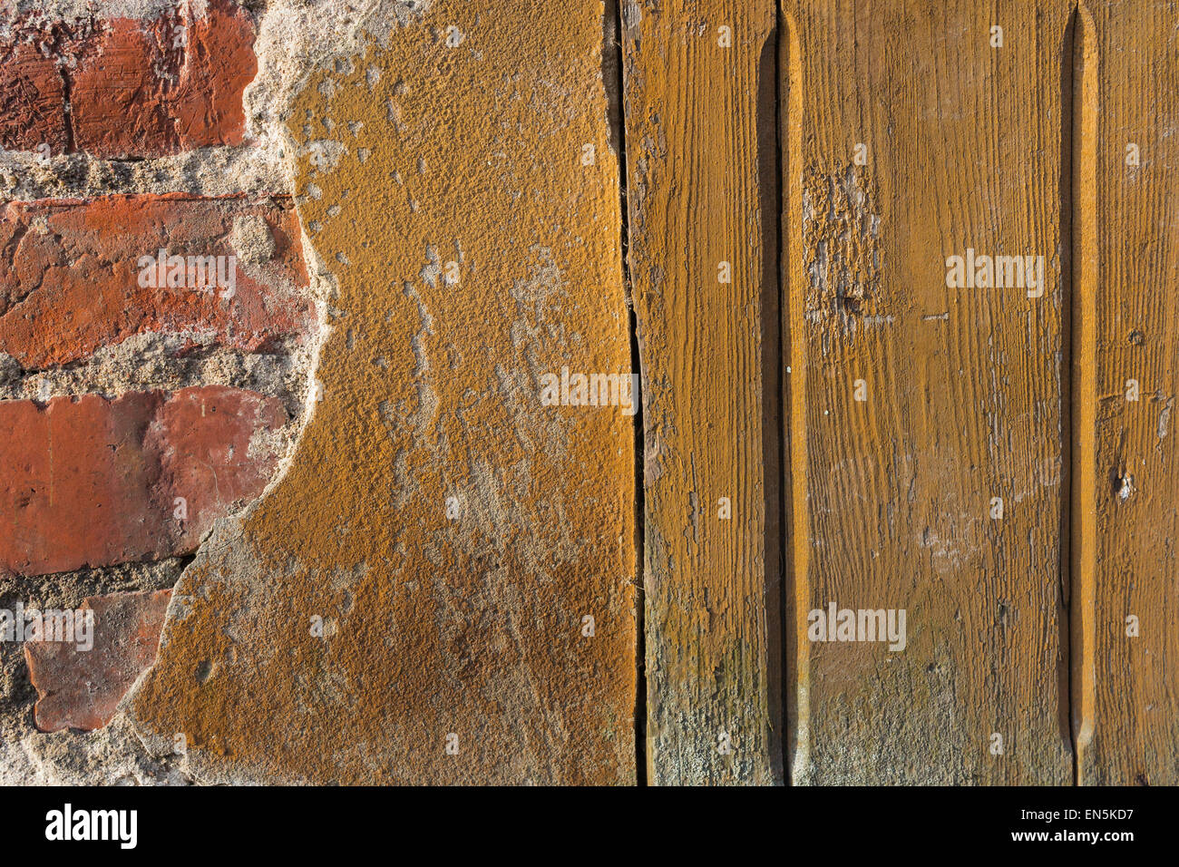 Old Broken Wall Planks Red Bricks Texture Background Closeup - Stock Image