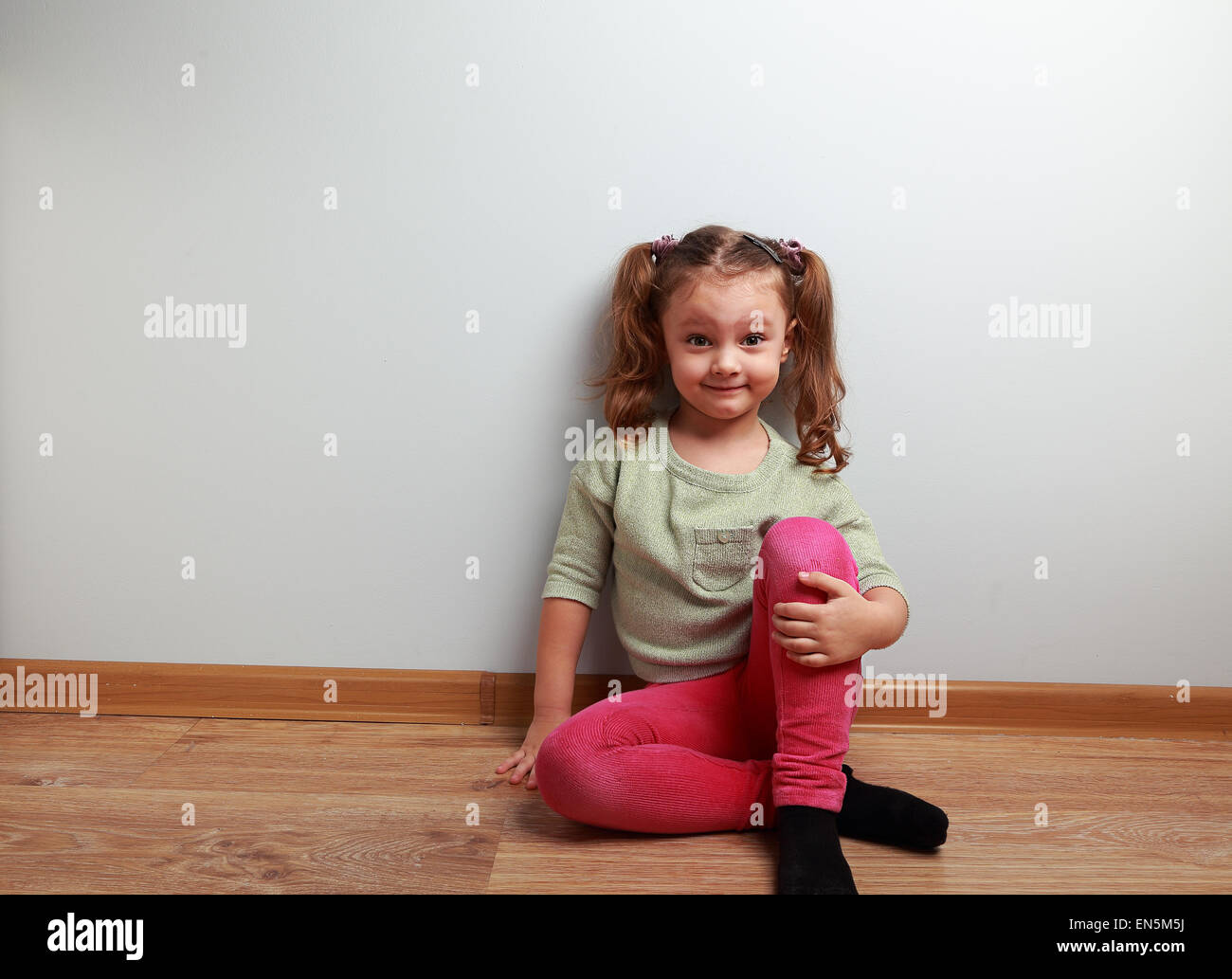 Fun grimacing girl sitting on the floor and smiling on blue wall background - Stock Image