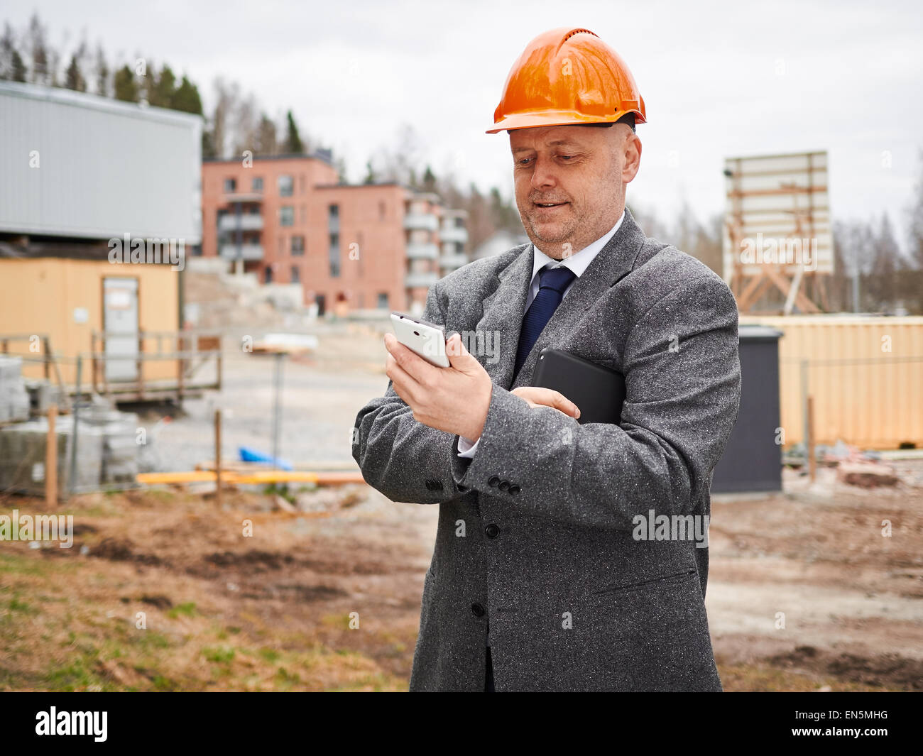 Male engineer uses cell phone, he wearing the suit and the hard hat, house construction site on background - Stock Image