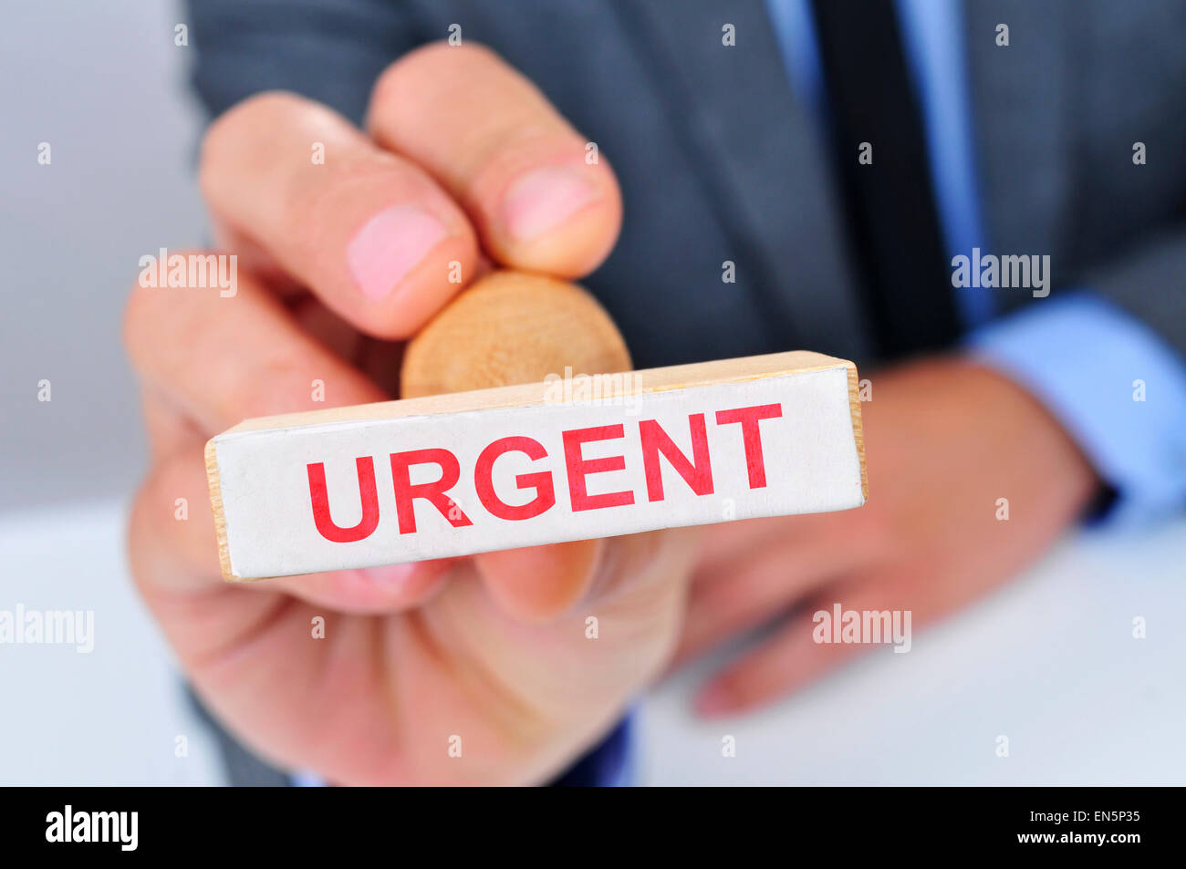 a young caucasian man at his office desk with a rubber stamp with the word urgent - Stock Image