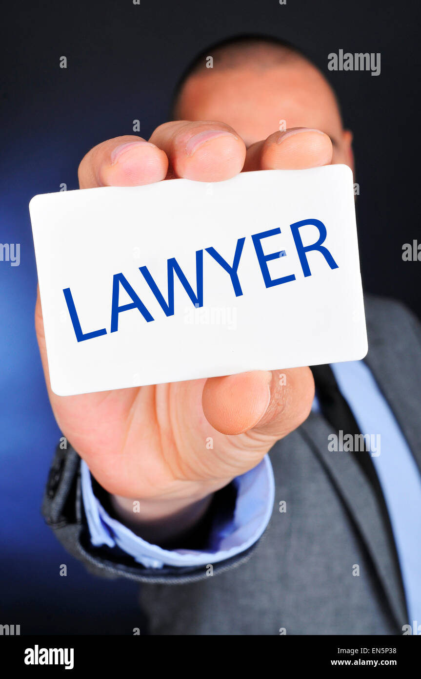 a young caucasian man wearing a gray suit shows a signboard with the word lawyer written in it - Stock Image