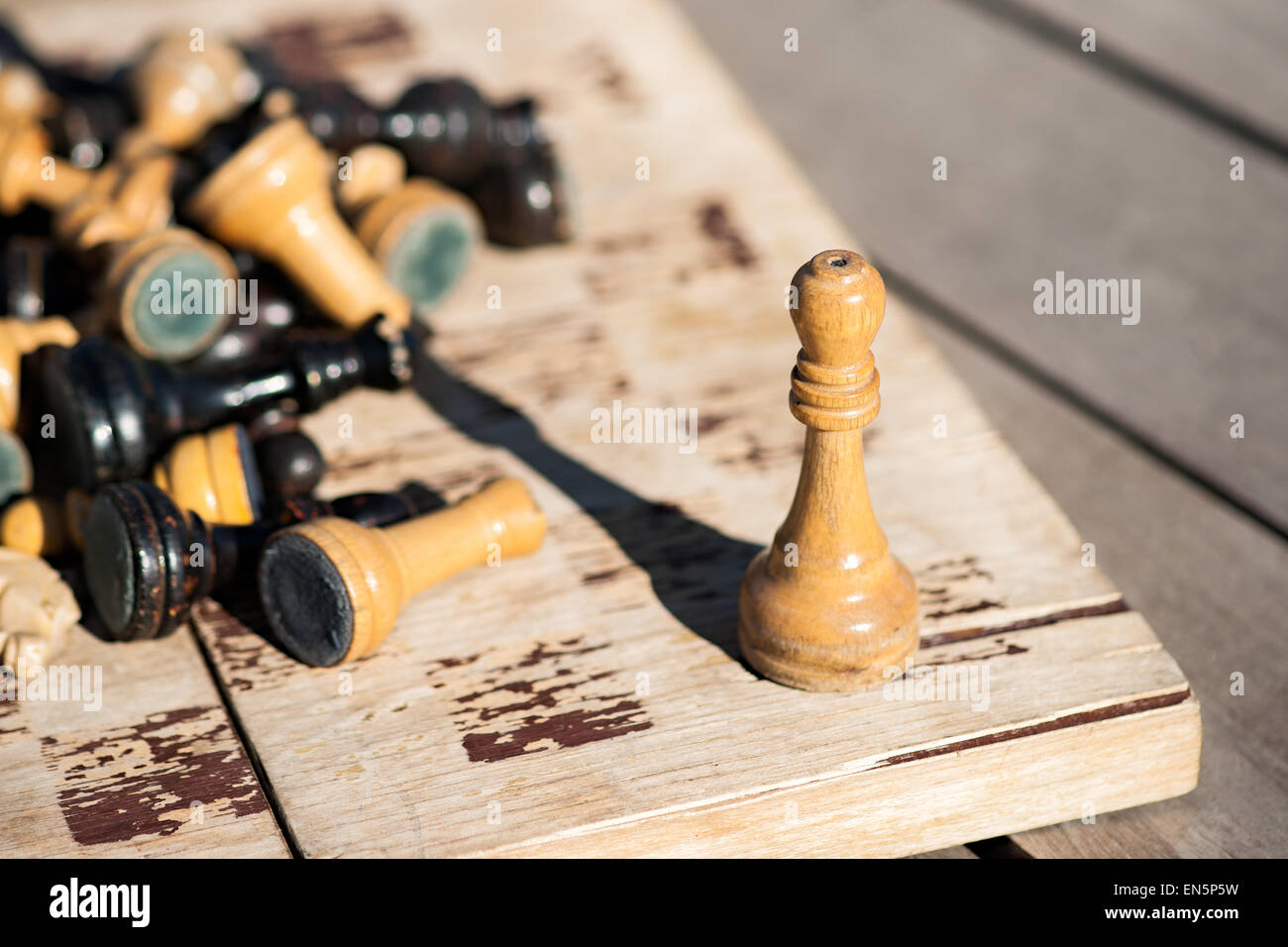 Old and withered wooden chess king on an old and withered chess board. Other chess pieces of black and white color - Stock Image