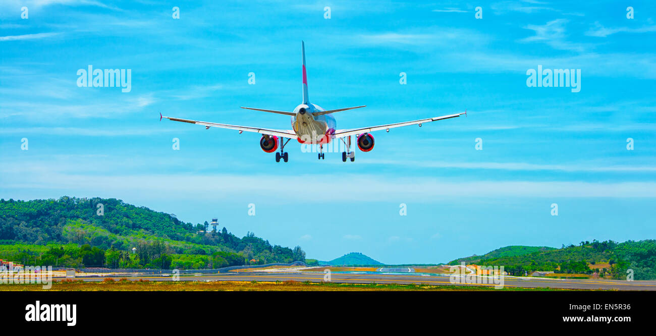 Twin-engine, commercial airliner coming in for a landing at an airport in a tropical, Southeast Asian country. A - Stock Image