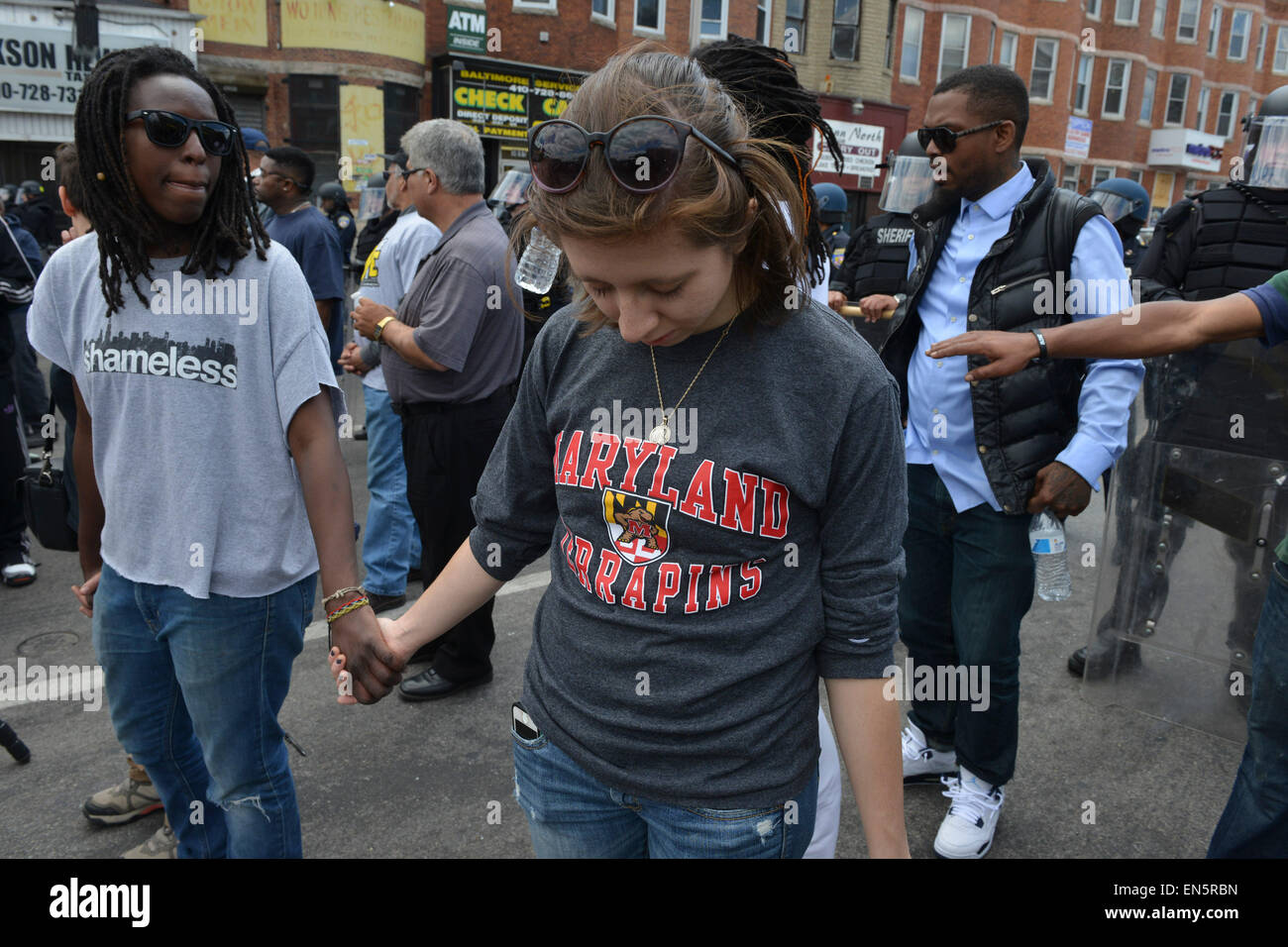 Baltimore, MD, Baltimore, Maryland, USA. 28th Apr, 2015. Neighbors and others advocating nonviolence stand in a - Stock Image