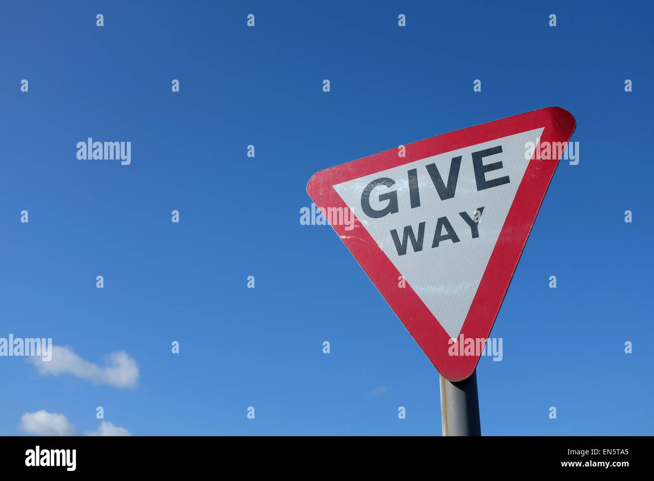 Give Way road sign against a blue background UK Stock Photo