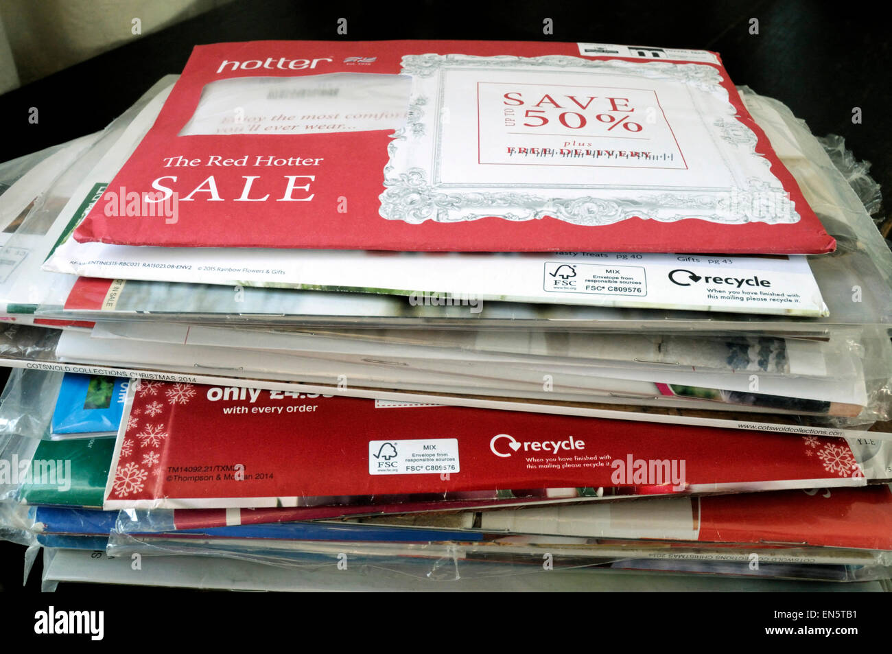 Pile of unopened envelopes containing clothing catalogues and showing recycle logo London, UK - Stock Image