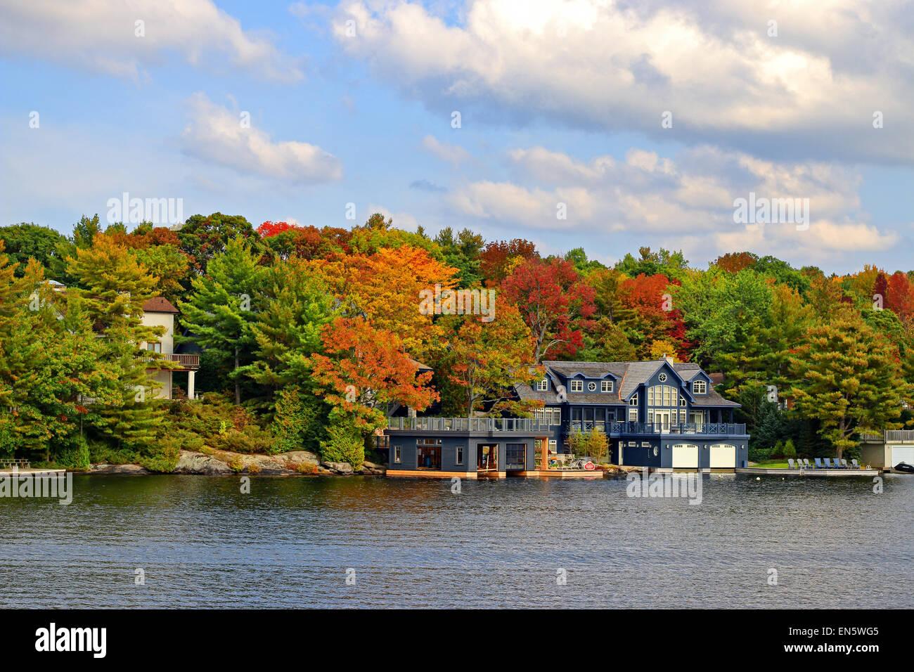 Million dollar cottages along Lake Moskoka near Gravenhurst, Ontario, in autumn. Photographed on a boat in Lake - Stock Image