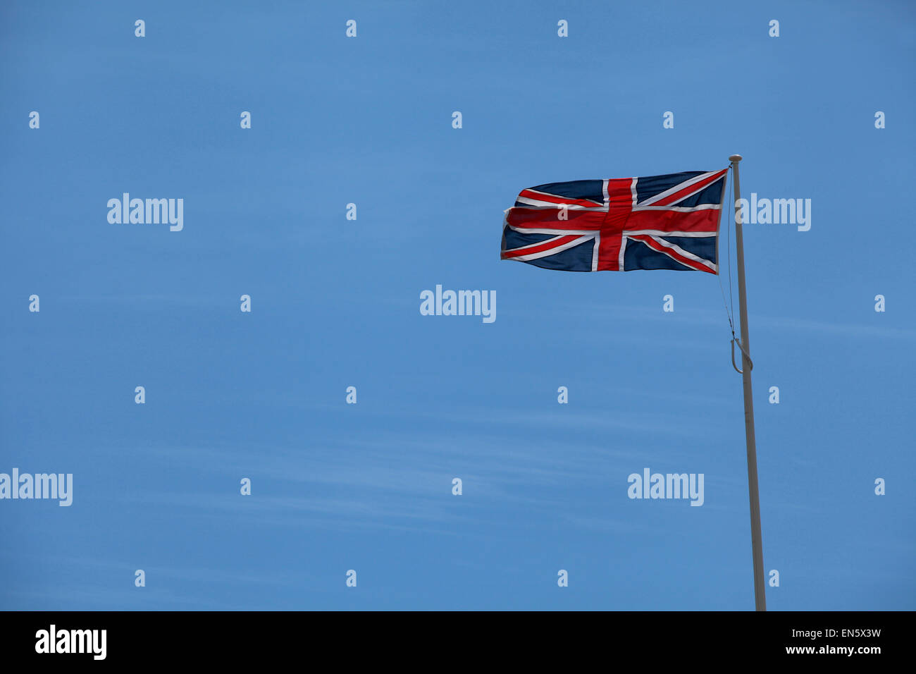 Union Flag flying against a blue sky with copy space - Stock Image