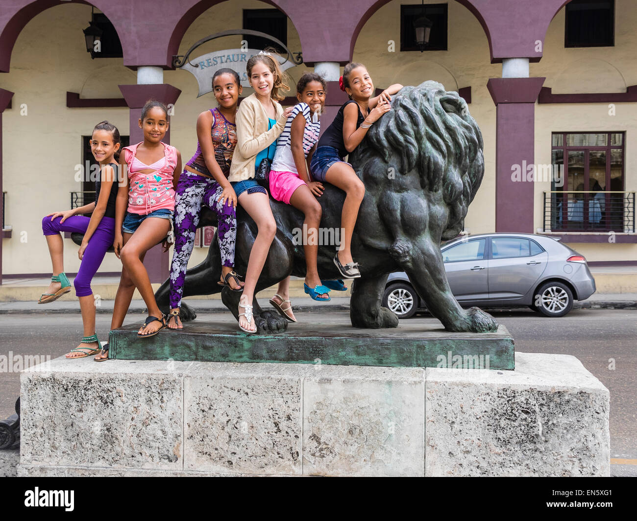 Six Cuban girls sit on a lion statue while posing for a photograph in Havana, Cuba. - Stock Image