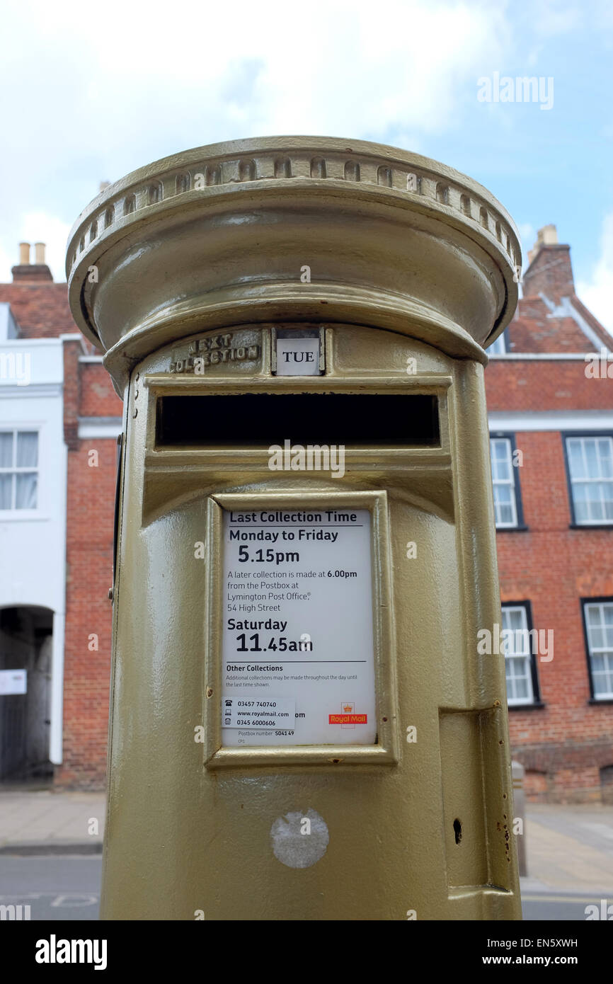 Golden Postbox in Lymington Hampshire painted gold to honour Ben Ainslie in the olympics - Stock Image